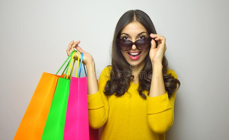 Image of a shocked young brunette lady wearing sunglasses posing with shopping bags and looking at camera over gray background. stock photography