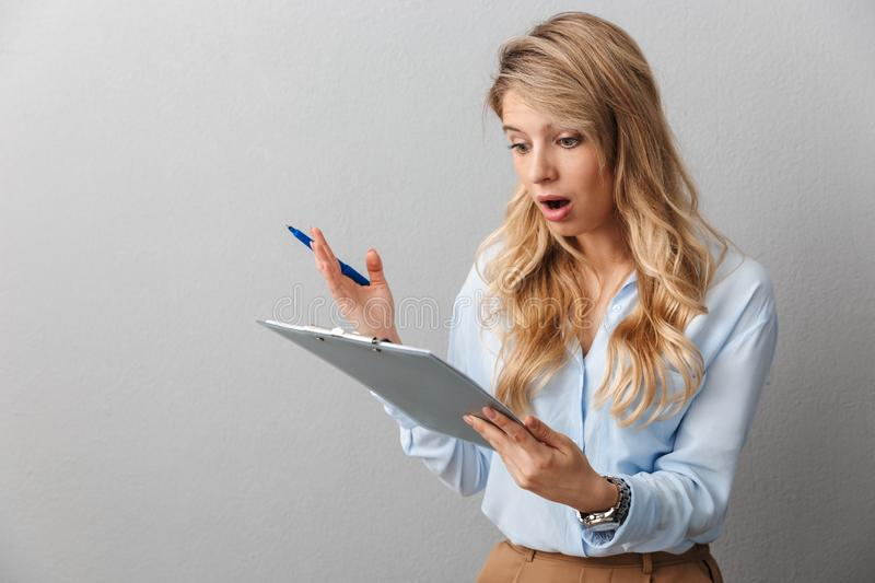 Shocked young pretty blonde business woman posing isolated grey wall background holding clipboard stock images