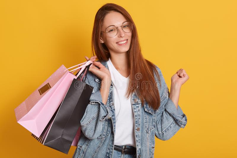 Image of shopping woman holding shopping black and rosy bags, looking directly at camera over yellow background, attractive lady. Wearing stylisj clothes and stock photos