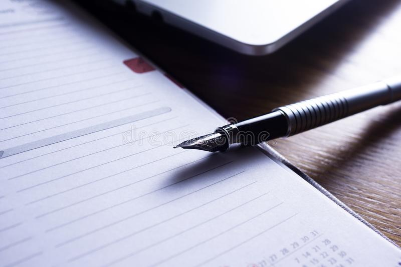 Image, showing a desk working space, with laptop, agenda, pen, phone royalty free stock images