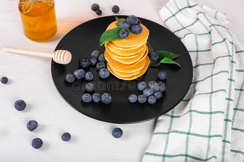 Image shows a homemade fluffy pancake with blueberry and mint on the top; situation is decorated with white wooden table and honey royalty free stock photo