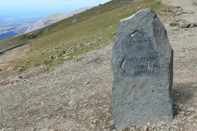 Snowdon marker post showing the Llanberis and Snowdon Ranger path. Image shows a marker post for the Llanberis path and the Snowdon Ranger path. The stone is royalty free stock photo