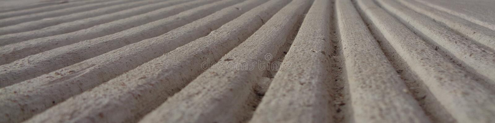 Parallel Lines Toward a Horizon; Optical Illusion. The image shows parallel lines in concrete. There is interest of texture, light and shadow. It shows royalty free stock photo
