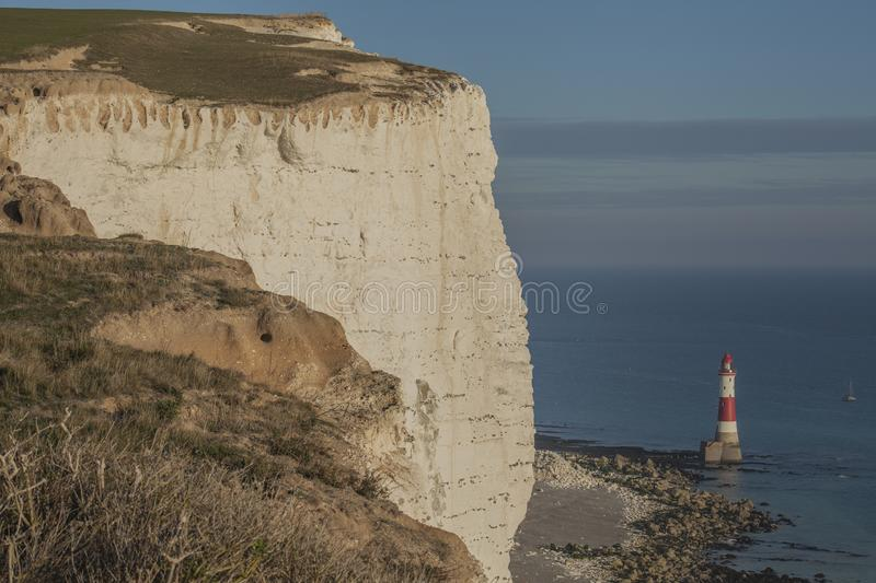 Seven Sisters, England, the UK - white cliffs, blue waters and seas; a lighthouse. This image shows some white cliffs in Seven Sisters, England, the UK. It was stock image