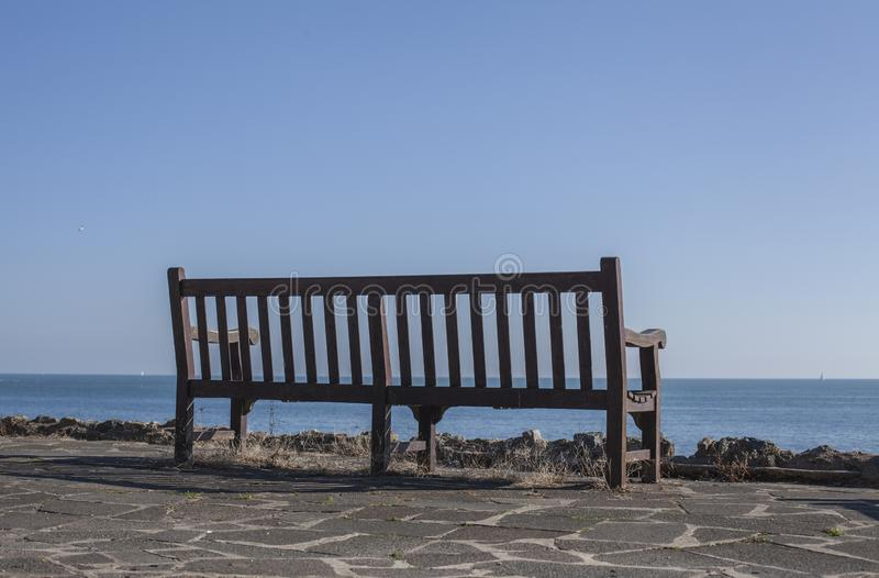 Eastbourne, England - blue skies and seas and a bench. This image shows a view of a beach in Eastbourne, England, the UK. Eastbourne is a resort town on England royalty free stock photo