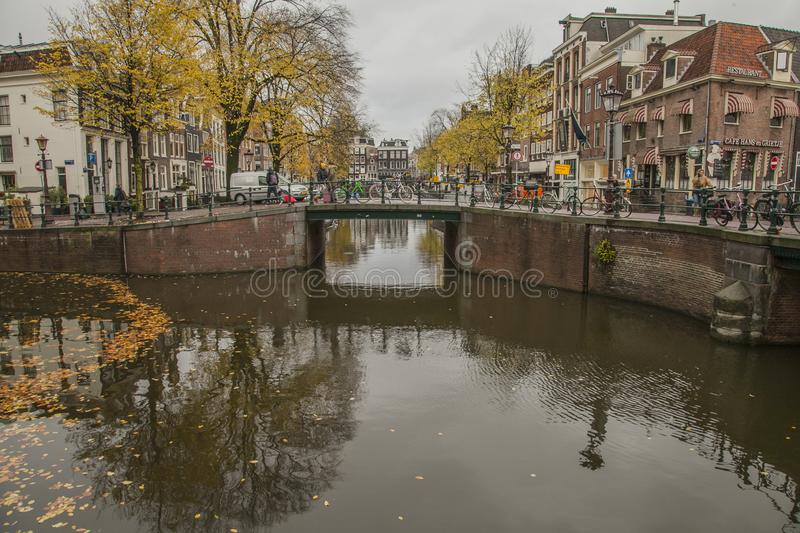 Amsterdam in autumn, canals and streets; yellow leaves. This image shows a view of a canal in Amsterdam. the Netherlands, Europe. It was taken on a cloudy day stock photo
