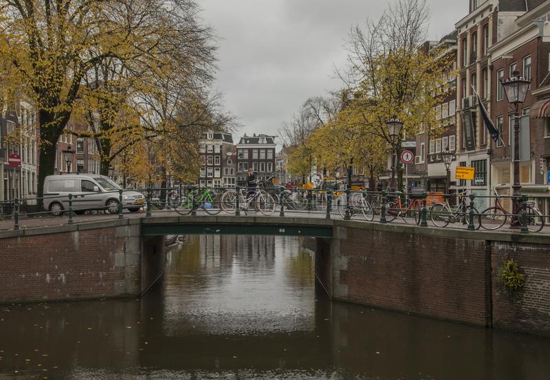Amsterdam in autumn, canals and streets; a cloudy day. This image shows a view of a canal in Amsterdam. the Netherlands. It was taken on a cloudy day in autumn stock photography