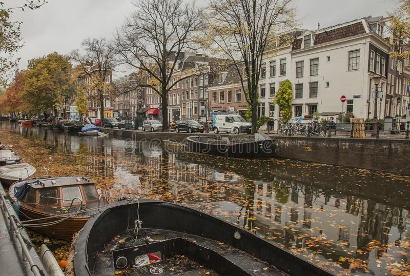 Amsterdam in autumn, canals and streets; a cloudy day. This image shows a view of a canal in Amsterdam. the Netherlands. It was taken on a cloudy day in autumn royalty free stock photos
