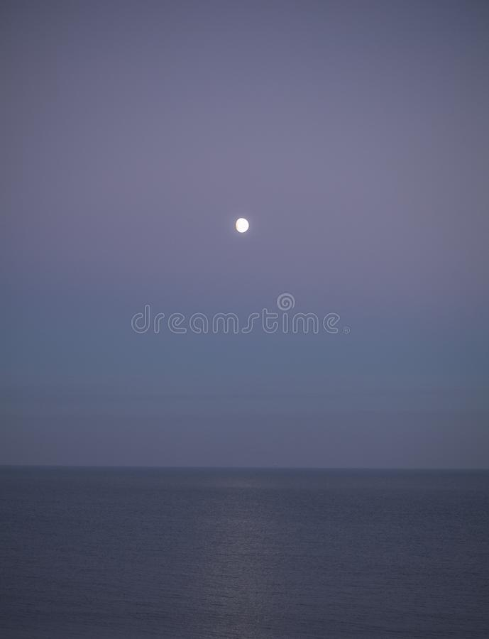 Eastbourne, East Sussex - the moon and purple skies. This image shows a view of the moon and some pink and purple skies in Eastbourne, East Sussex, England. It royalty free stock photography