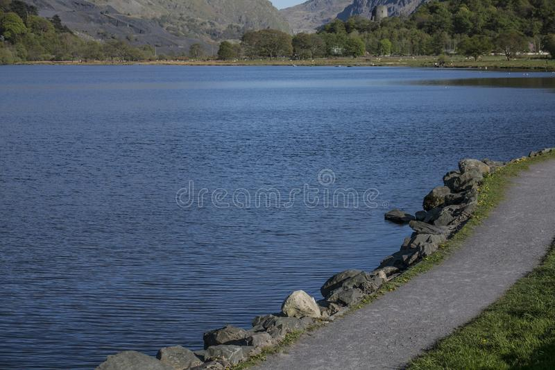 Llanberis, North Wales - blue waters of a lake. This image shows a view of some blue waters of a lake in Llanberis, North Wales; with some hills in the royalty free stock photos