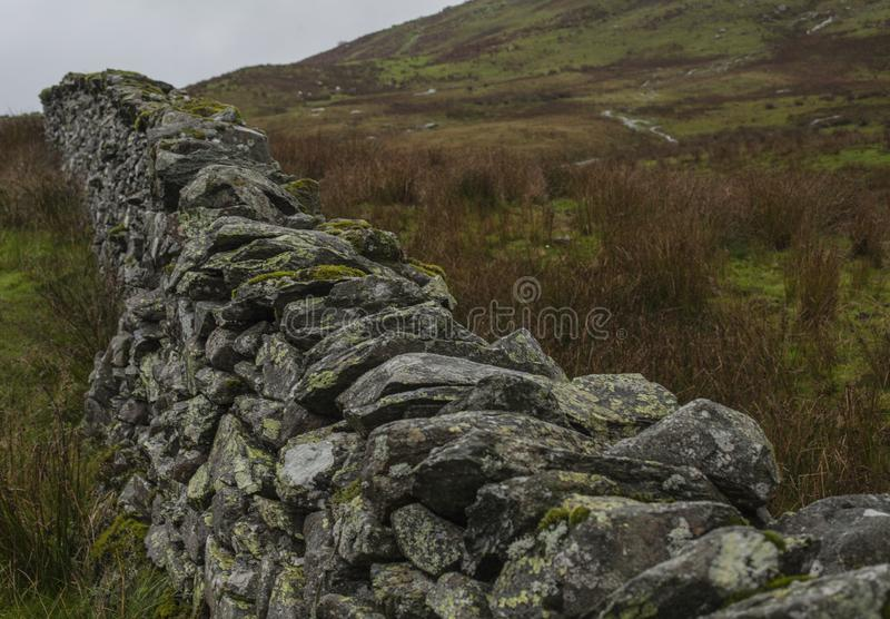 Lake District, Cumbria, England - autumn on a cloudy day, a stone fence. This image shows a view of some fields and meadows in Cumbria, Lake District, England royalty free stock images