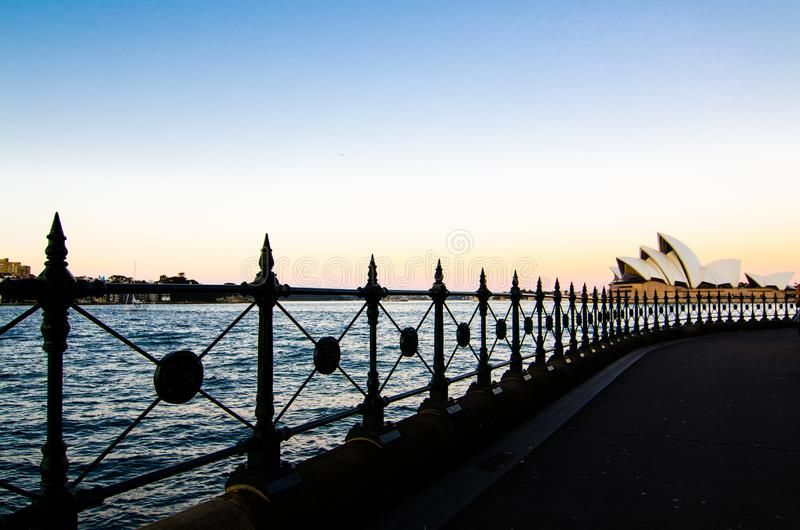 The image shows the view of Sydney harbour and Sydney Opera house from sidewalk under the harbour bridge at twilight time sky. royalty free stock photography