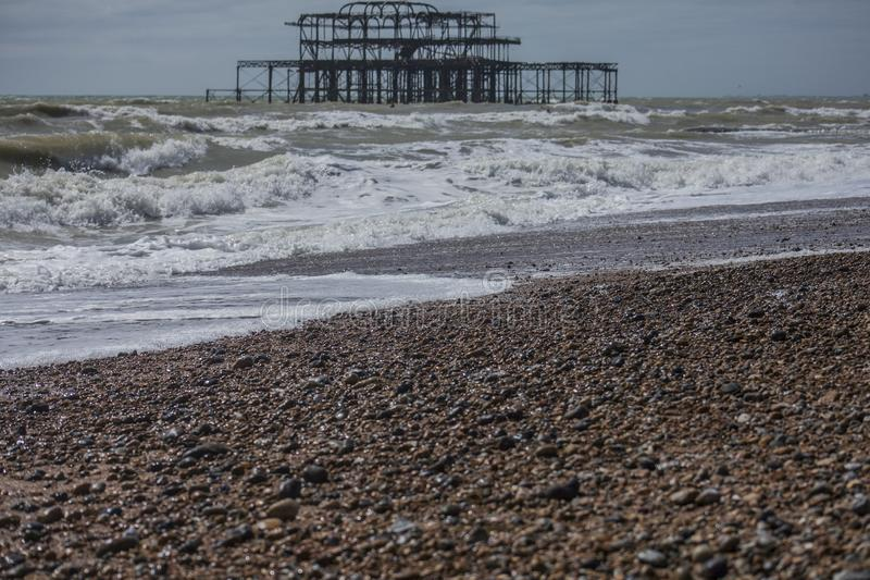 West Pier, Brighton, England - the waves and the beach. This image shows a view of the West Pier. The West Pier is a pier in Brighton, England, the UK. It was royalty free stock images