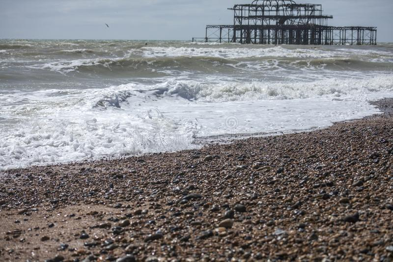 West Pier, Brighton, England - the waves and the pebbles. This image shows a view of the West Pier. The West Pier is a pier in Brighton, England, the UK. It was royalty free stock photos