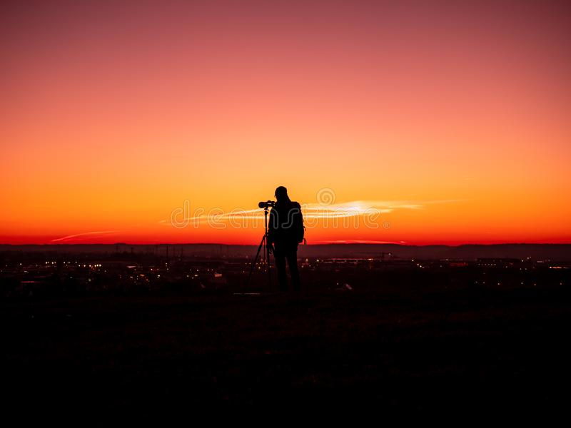 Image of a silhouette of a man with tripot and camera standing on a hill during colorful sunset royalty free stock image