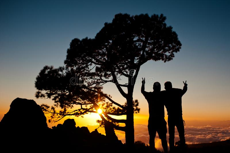 Silhouette of two friends enjoying the sunset on the mountain, encompasses and shows the sign of peace. stock photo