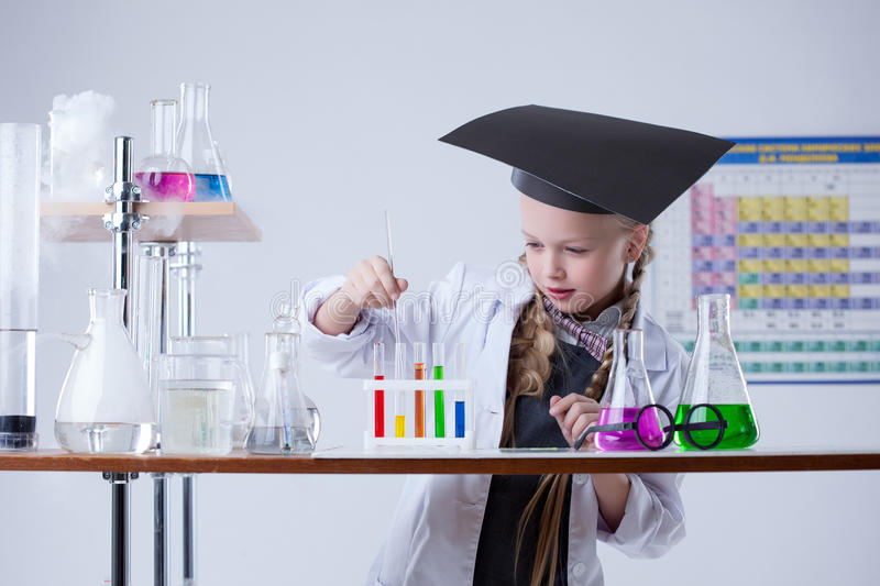Image of smart little girl mixes reagents in lab royalty free stock photography