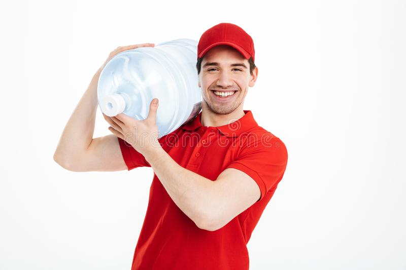 Image of smiling bottled water delivery courier in red t-shirt a. Nd cap carrying tank of fresh drink over white background royalty free stock images