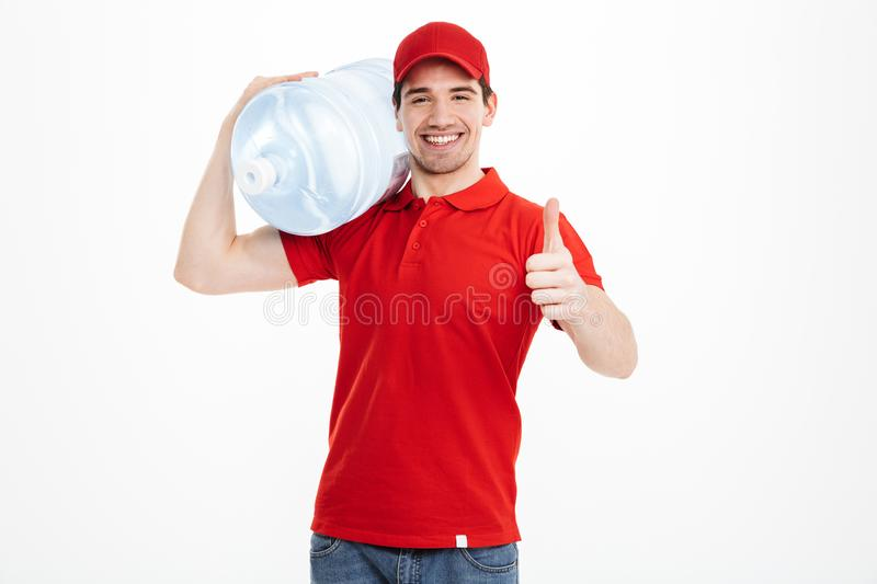 Image of smiling bottled water delivery courier in red t-shirt a. Nd cap carrying tank of fresh drink and showing thumb up over white background stock images