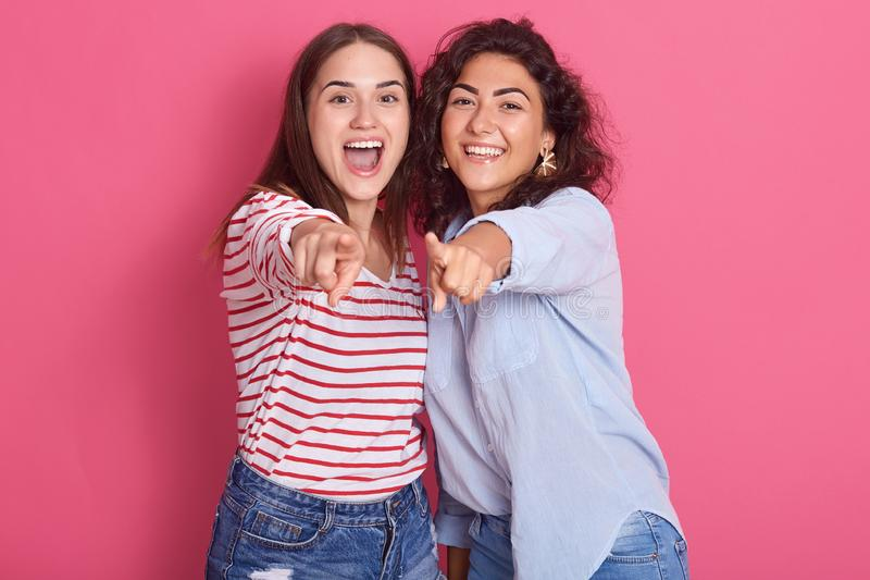 Image of smiling breunette girls posing isolated over pink sudio background, looking amd pointing at camera, female with wavy hair stock photography