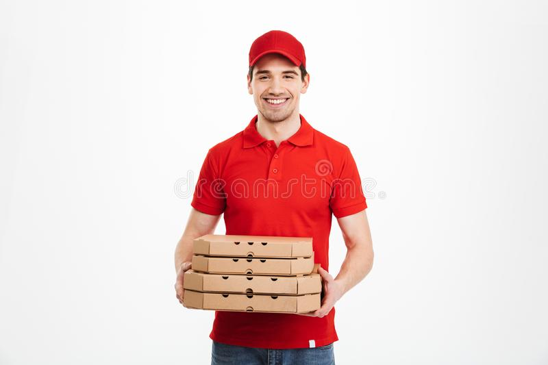 Image of smiling deliveryman in red t-shirt and cap holding stack of pizza boxes, isolated over white background royalty free stock photo