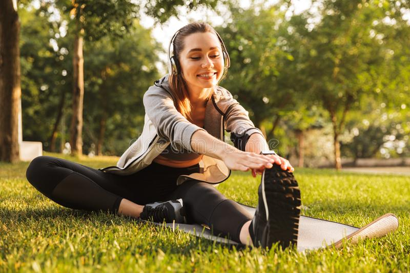 Image of smiling fitness woman 20s wearing headphones working out and stretching legs, while sitting on exercise mat in green park stock photography