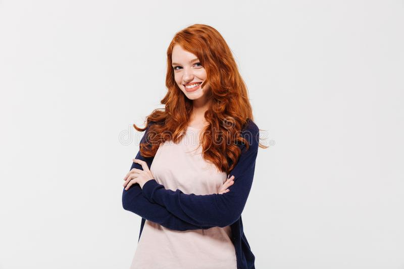Smiling pretty young redhead lady with arms crossed. stock photos