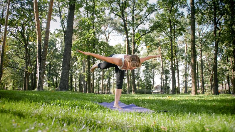Photo of smiling woman doing yoga and fitness exercises. Middle aged people taking care of their health. Harmony of body stock image