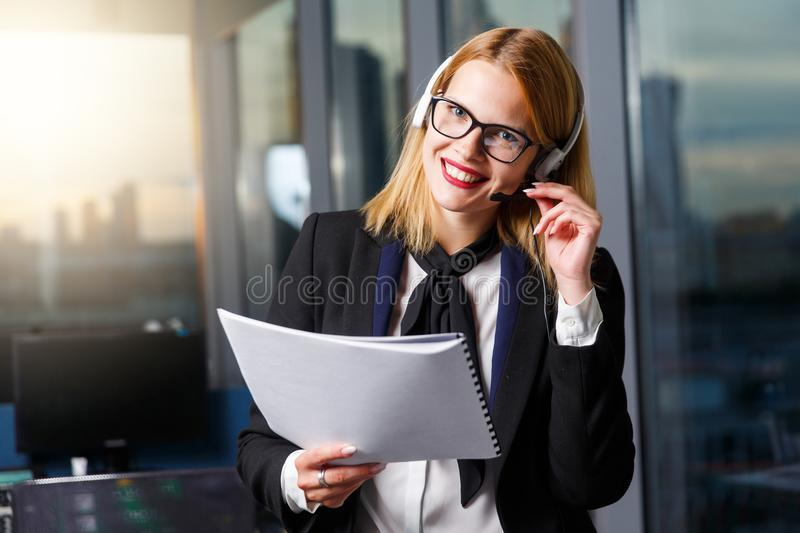 Image of smiling woman with glasses and headphones with paper in hands near glass wall stock photo