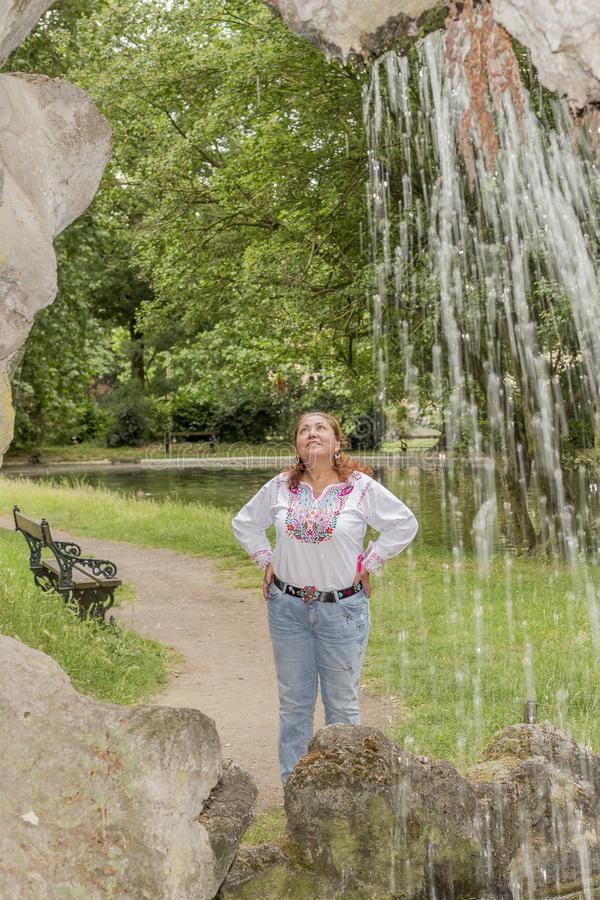 Image of a smiling woman next to a small waterfall looking up in the citadel park. In Ghent Belgium on a wonderful and cloudy day to visit in the city royalty free stock photo