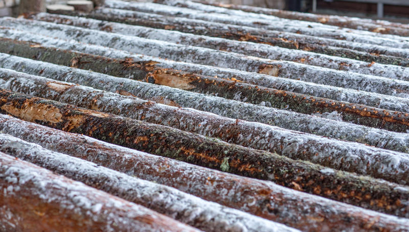 Image of snow-covered logs at sawmill royalty free stock photo