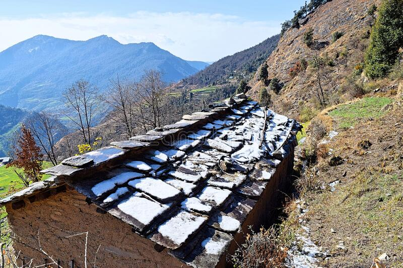 Snow on Roof of a Hut in a Village with Himalayan Mountains in Background - Winter in Himalayas, Uttarakhand, India stock photo
