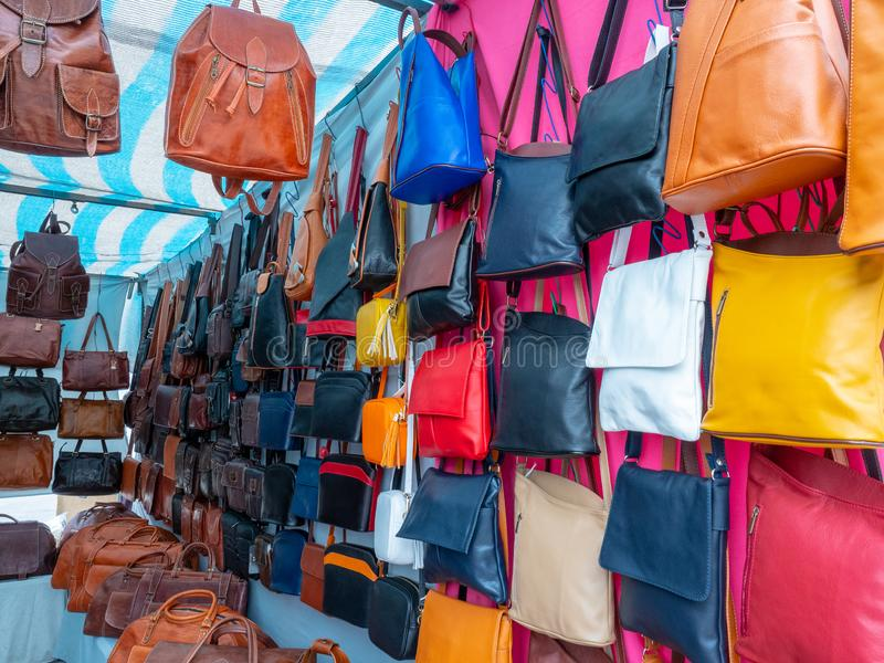 Bags of various colours and types in a flea market. Image of some bags of various colours and types in a flea market stock photo