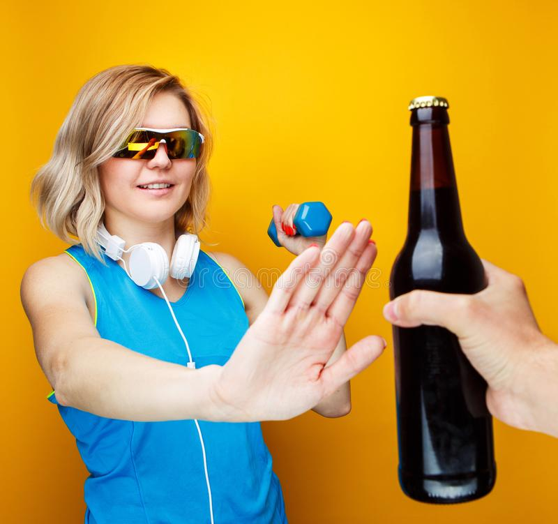 Image of sporty woman with dumbbell refuses from bottle of beer in studio. Image of sporty woman with dumbbell refuses from bottle of beer in studio on orange royalty free stock image