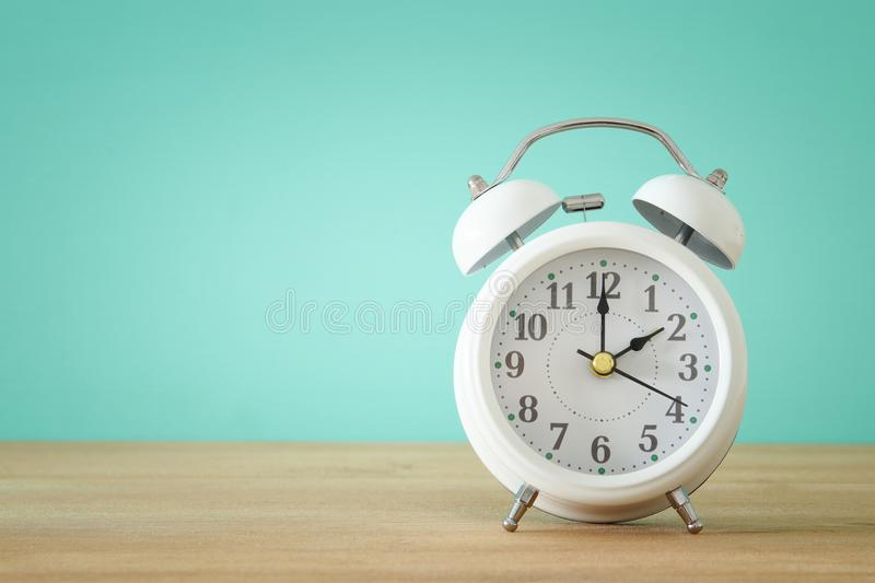 Image of spring Time Change. Summer back concept. Vintage alarm Clock over wooden table. stock image