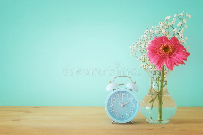Image of spring Time Change. Summer back concept. Vintage alarm Clock over wooden table. Image of spring Time Change. Summer back concept. Vintage alarm Clock royalty free stock images