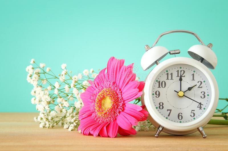 Image of spring Time Change. Summer back concept. Vintage alarm Clock over wooden table. royalty free stock images