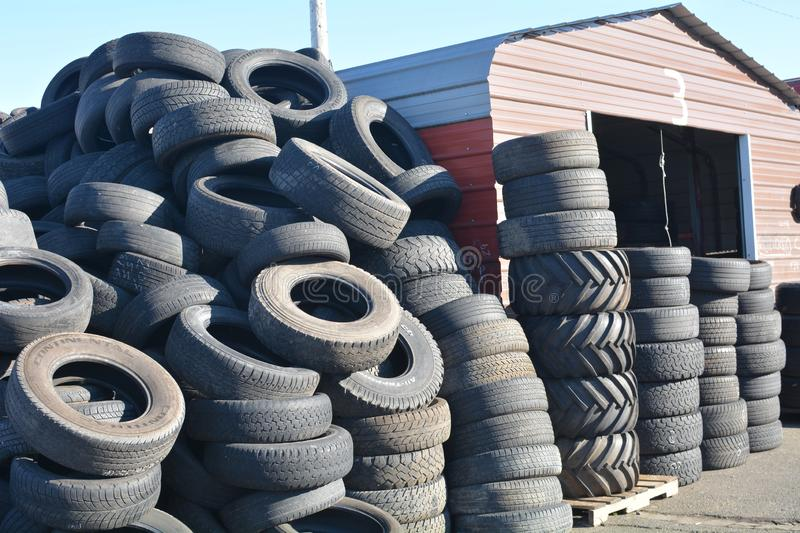 Stacks of black tires in Salem, Oregon. This an image of stacks of black tires in front of a shed at a tire store in Salem, Oregon stock photo