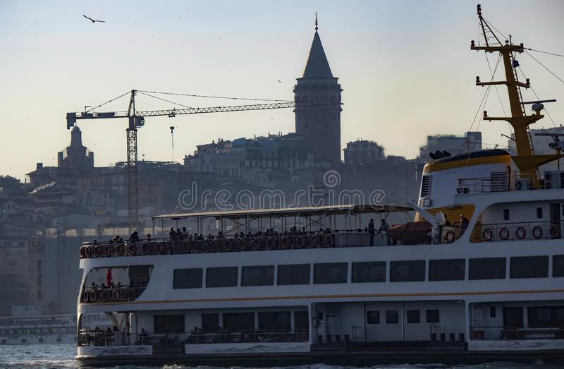 Image of steamship at sea and silhouette of Galata tower in background. Tour, old, famous, building, istanbul, travel, tourism, turkish, city, turkey royalty free stock photography
