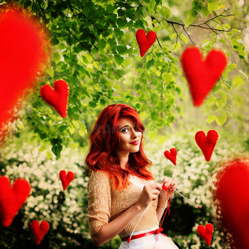 The image in the style of fantasy Valentine's Day. Young beautiful girl knits red hearts that fly around it. The image in the style of fantasy Valentine's Day royalty free stock photos