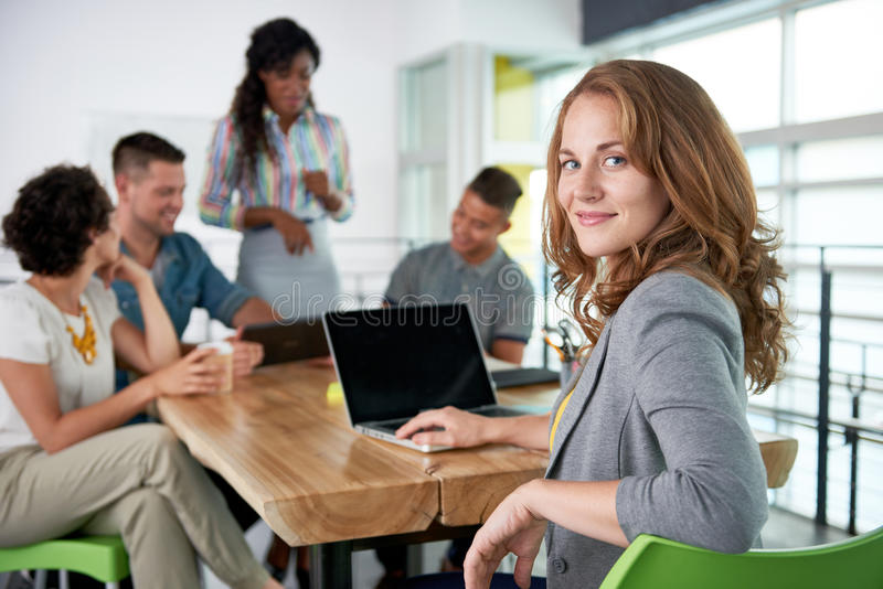 Image of a succesful casual business woman using laptop during meeting royalty free stock image