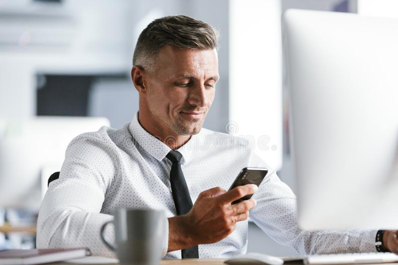 Image of successful businessman 30s wearing white shirt and tie stock photography