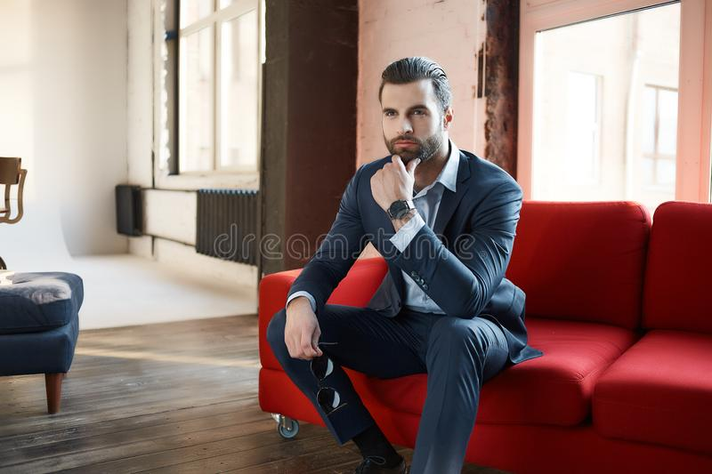 Image of successful and confident young businessman who is looking away thoughtfully and sitting on comfortable office. Sofa. Business look. Success concept royalty free stock image