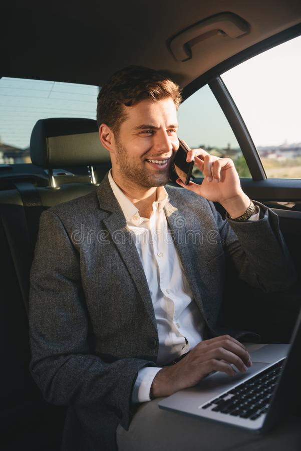 Image of successful director man in suit talking on smartphone a. Nd working on laptop while back sitting in business class car royalty free stock photos