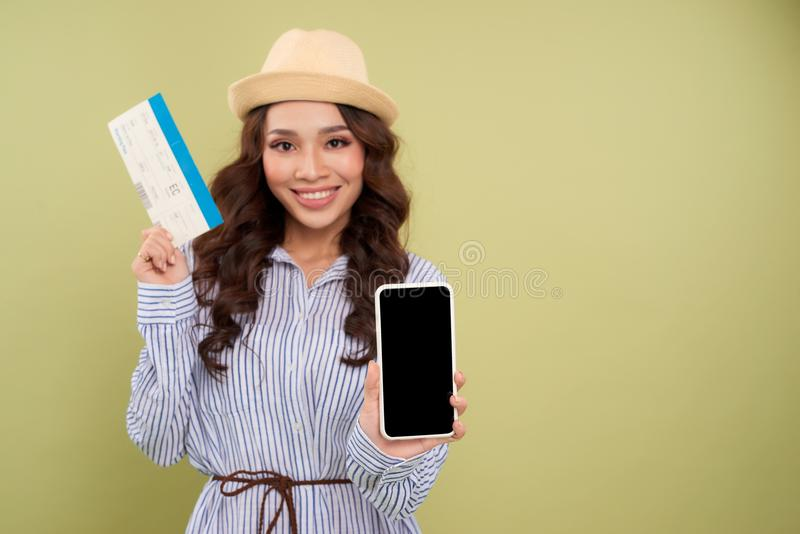 Image of successful voyage girl 20s expressing delight while holding air tickets and smartphone in hands isolated over green back royalty free stock image