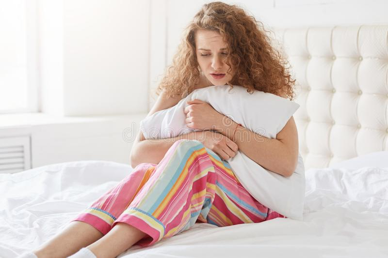 Image of suffering tender female pressing her pillow close to body, sitting on white bed, wearing striped pyjamas, feeling unwell stock images