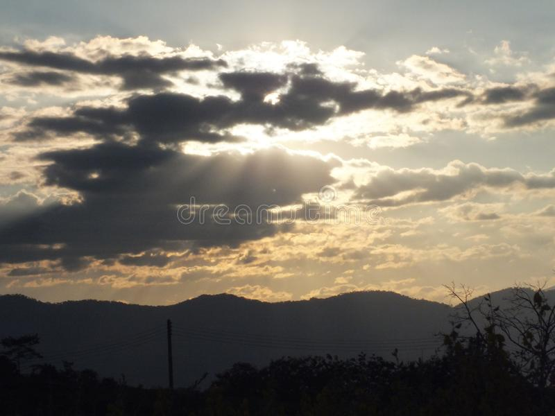 The image of the sun hiding behind the clouds saw a golden glow. royalty free stock image
