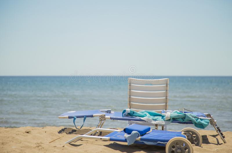 Image of sun lounger and white plastic chair on the beach. With sea and background stock photo