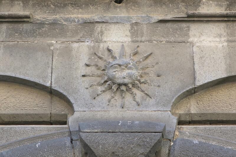 Image of the sun on a wall above a door in Orvieto Italy stock image