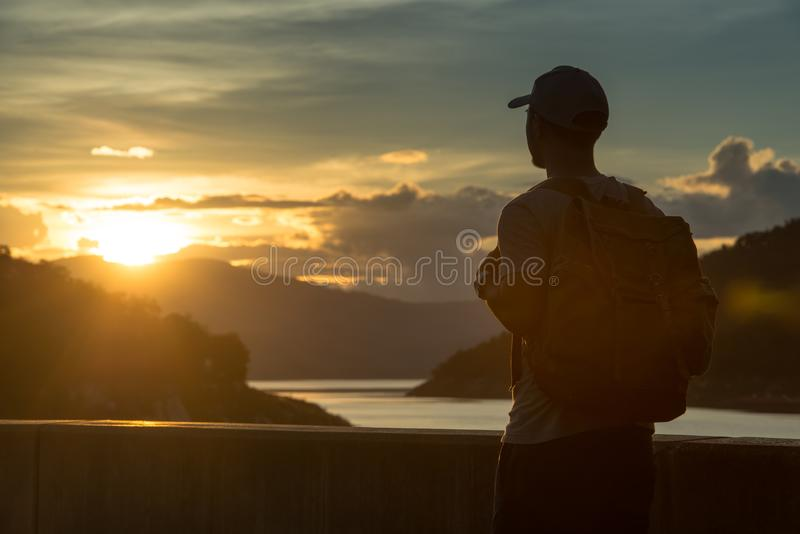 Image of sunrise with a silhouette of a tourist man in natural surrounding stock photos